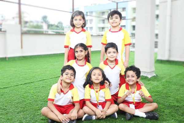 Students of one of the best school in pune sitting in a ground